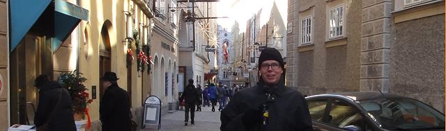 Gatelangs i Salzburg med varm drikke i koppen