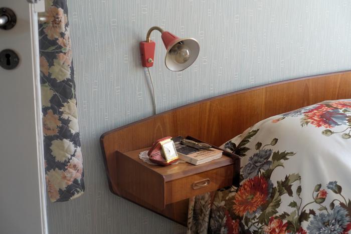 Detaljer fra det innebygde teak-nattbordet. Jeg kjenner igjen det reisevekkeruret.